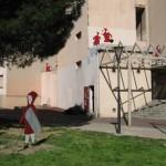 """""""Loup y es-tu?"""", 2011, contreplaqué marine,  acier, peinture, 8 silhouettes de petits Chaperons Rouges de Sécurité (dimensions variables), 1 silhouette de Loup, 200 x 40 x 1,5 cm, Exposition collective """"J'explose"""" avec Entrez sans frapper à  Toulouse (Empalot)."""